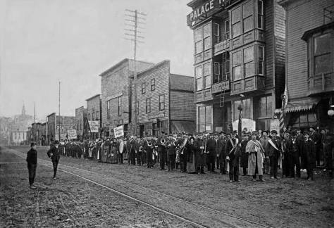 "The Salvation Army band posing on Jackson Street in front of the Palace Theatre, possibly during or following a ""battle of the bands"" with the house orchestra. The subject looks east from Commercial Street (First Ave. S.)."