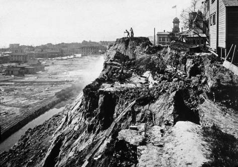 Circa 1910, cliff formation to the east side of Fifth Avenue. The surviving center-section of Denny School appears to the right of the couple working at the cliff-top. The view looks north.