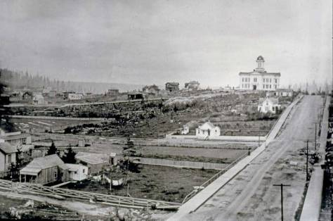 Battery Street looking east from the rear balcony of the Bell Hotel at the southeast corner of Front Street (First Ave.) and Battery Street ca. 1887-88. Denny School (1884) stands in the distance at the northeast corner of Fifth Avenue and Battery. Photo by Mumford.