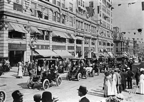 A line-up of electric cars passing the Central Building in the 1911 Potlatch parade. (Courtesy, Michael Maslan)