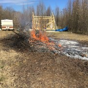 Brush pile burning with cabin in background