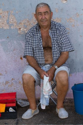 man sitting on stool with towel in his hands wearing plimsoles