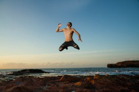 young man with torn trousers at sea jumping in air without shirt