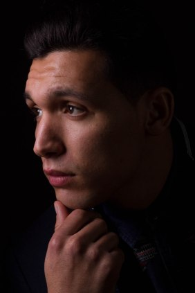young man in profile against black background