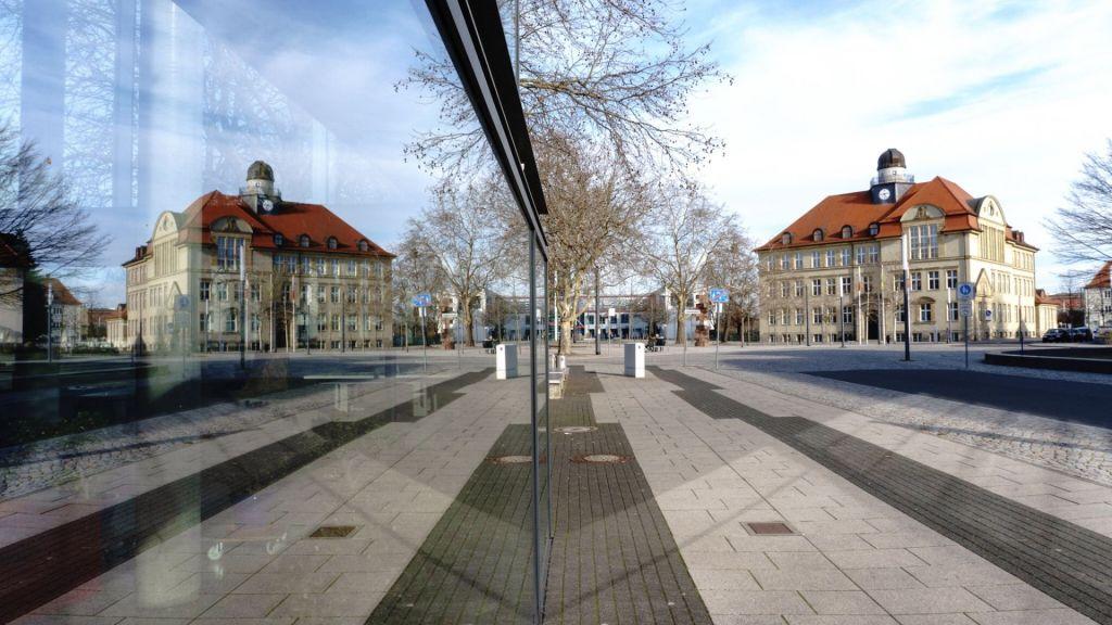 In einer Glasfassade spiegelen sich die Gebäude
