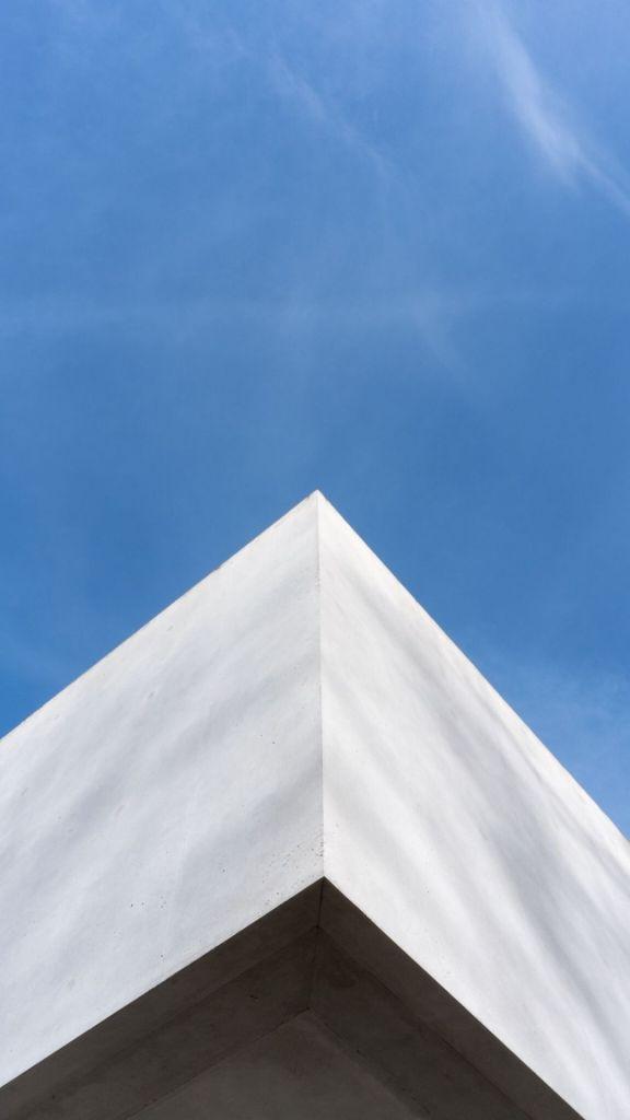 Ein Gebäudekante wie ein Schiffsbug vor blauem Himmel