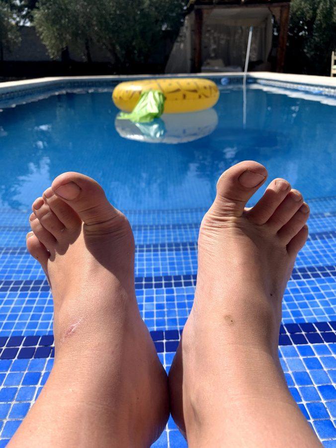 Mis pies con la piscuna de fondo