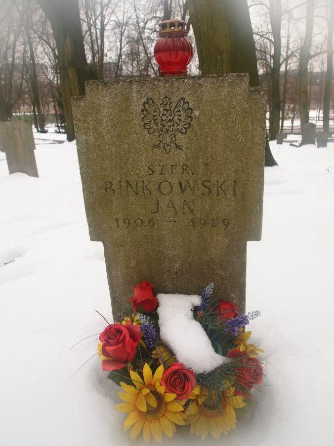 Tumba con nombre polaco cubierta de nieve con flores en la Ciudadela de Poznan