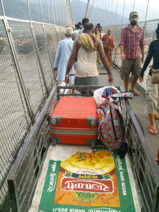 Hombre tirando de carreta con mi equipaje cruzando un puente sobre el Ganges