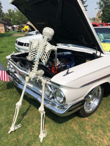 skeleton working on old car