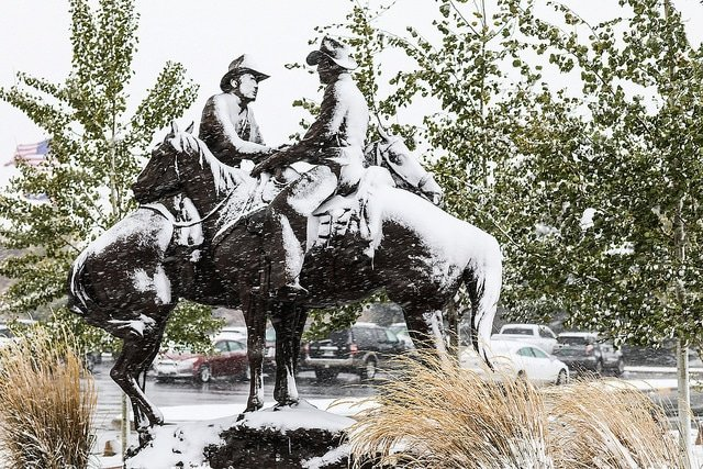 cowboy statues covered in snow.