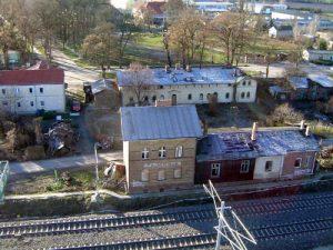 Die dem Verfall preisgegebenen Häuser direkt an der Bahn gehören zu Paulinenaues ältesten Gebäuden. Im Hintergrund der Kleine Sportplatz und das Institutsgelände.