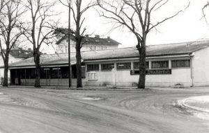 Der Konsum Anfang der 1980er Jahre. Aus dieser Perspektive ist deutlich zu erkennen, wie unglücklich das Gebäude im Ortsbild positioniert ist. Eigentlich sollte die Bahnhofstraße als Sichtachse direkt auf den Bahnhof zulaufen.