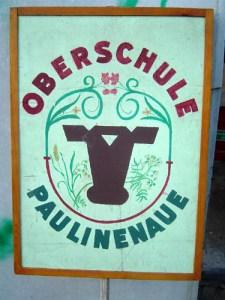 Auch die Schule hatte ihr Schild. Das Motiv ist eine Bearbeitung des von Georg Drasché entworfenen Paulinenaue-Wappens.