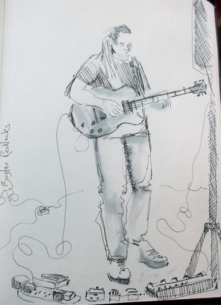 Buster Redlocks plays his guitar. Pauline Williams, local artist, draws.