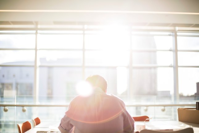 Man working in an office with the sun over his shoulder
