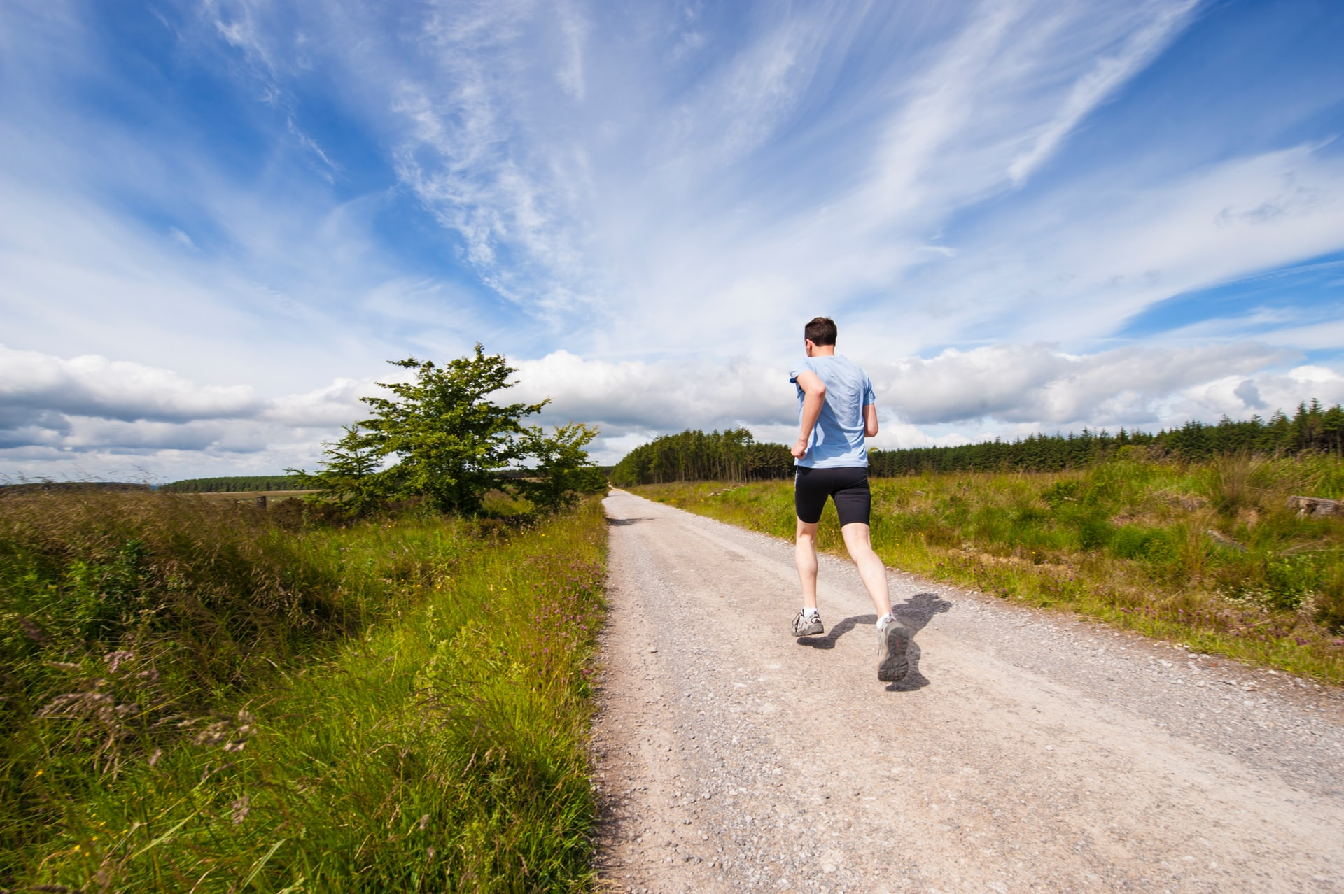 Man running along a sand road