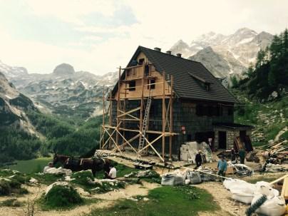 Vodnikov Dom clad with scafolding, Mt Triglav behind