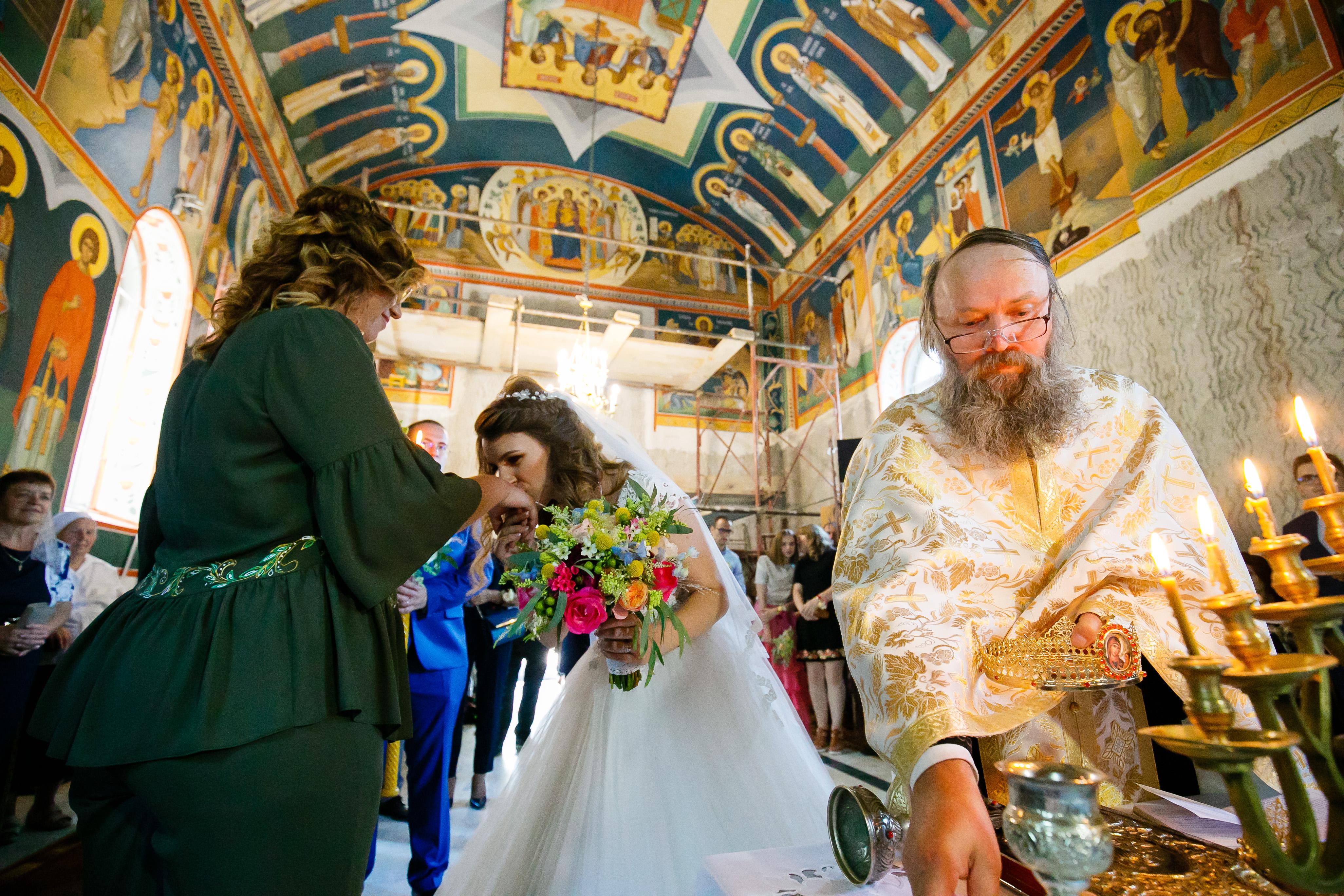 Alexandra si Vlad nunta iasi cununia religiosa mireasa saruta mana nasei - fotograf profesionist nunta