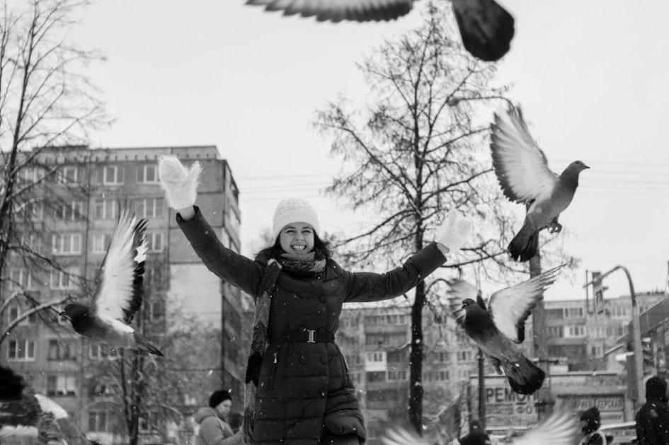 Девушка, бегущая через голубей