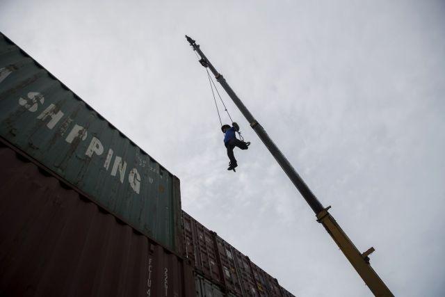 Radnik na glavnoj dizalici krana, visoko nad složenim kontejnerima skladišta u Bangkoku, 21. jul (Brent Lewin/Bloomberg)