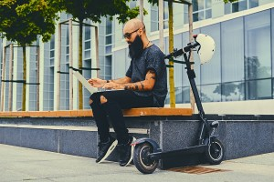 Shaved head tattooed, bearded male using a laptop over modern building background after the electric scooter ride.