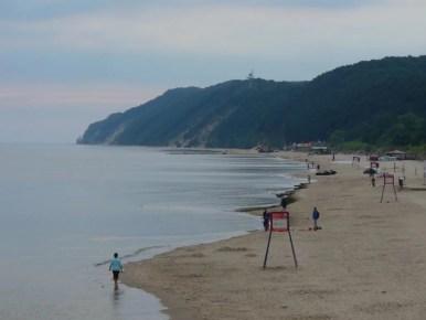 plaża nad morzem bałtyckim w międzyzdrojach, w oddali klify wolińskiego parku narodowego