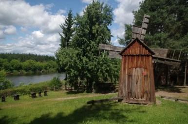 skansen budownictwa kurpiowskiego w nowogrodzie, na pierwszym planie widoczny wiatrak, w tle rzeka narew