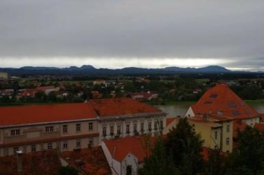 widok spod zamku w ptuju na drawę i góry w oddali