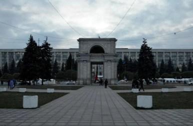 łuk triumfalny w kiszyniowie w mołdawii, w tle budynek parlamentu mołdawii