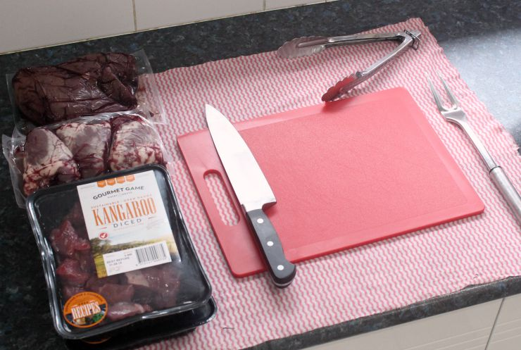 raw kangaroo meat and organs alongside knife, tongs and red chopping board
