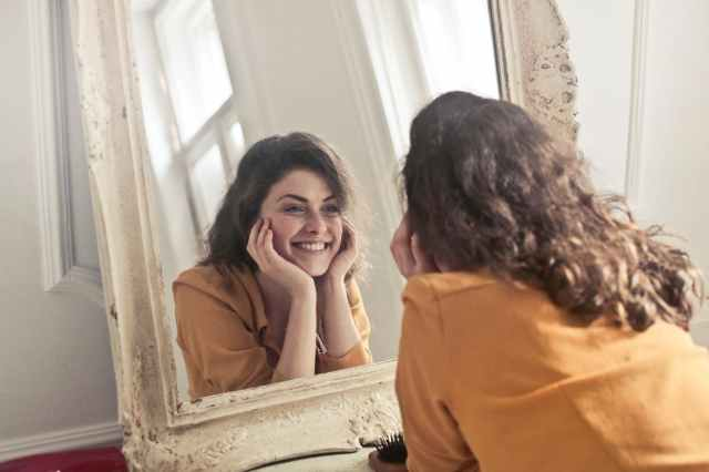photo of woman looking at the mirror and smiling