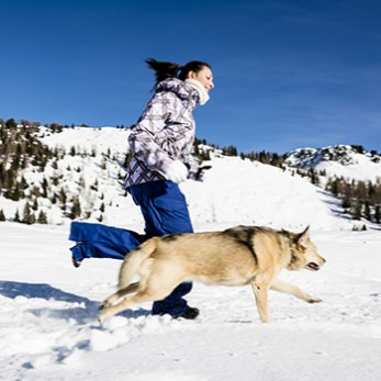 Girl Running In Snow With Dog In a Mountain Landscape