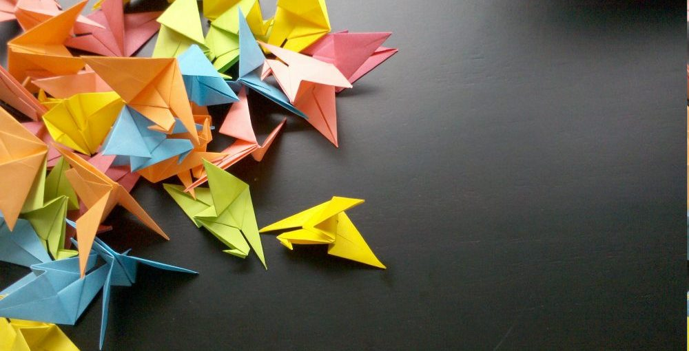 Paper origami cranes on grey background.