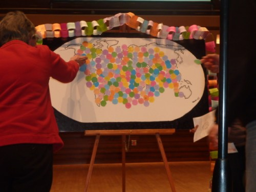 Participants in the World Peace Day Interfaith Prayer Service add their piece of colored paper to the map of the world.