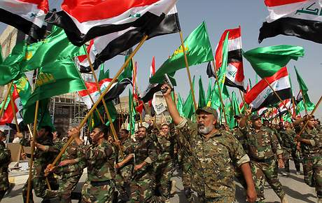 Iraqi Shiite fighters parade with weapons and national flags on June 21, 2014 in the capital, Baghdad. Shiite fighters paraded in Baghdad and south Iraq in a dramatic show of force aimed at Sunni militants who overran swathes of territory in a crisis threatening to rip the country apart.  AFP PHOTO