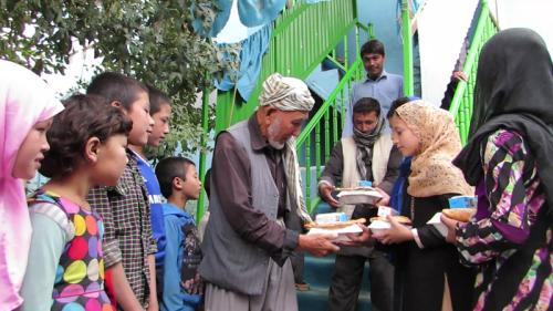 "The Borderfree Street Kids sharing the food with the Afghan laborers, and saying to them, ""Come again in happiness!"""