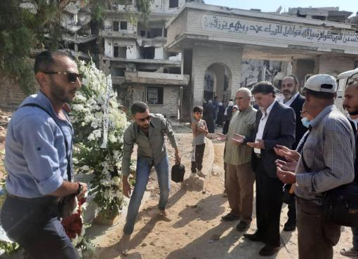 أكاليل من الزهور على أضرحة الشهداء في مخيم اليرموك باسم الرئيس