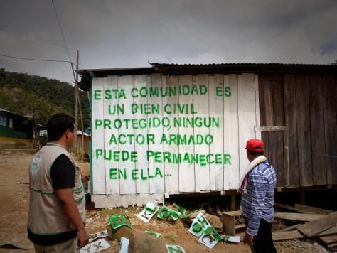 Yesid Triana (CREDHOS) y Andrés Ortiz (CREDHOS) pintan un mensaje en un muro en la Comunidad de Mina Walter, San Pablo, Sur de Cesar durante un aco
