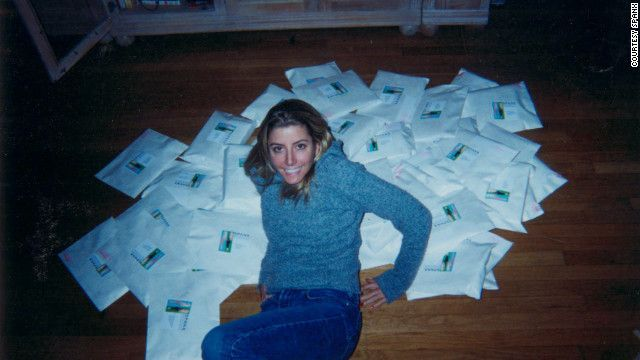 A picture of the young Sara Blakely, founder of Spanx, in the late 1900s. She is wearing a blue sweater and blue jeans. She is sitting on a pile of envelopes on a hardwood floor. These are products she is shipping out to customers.