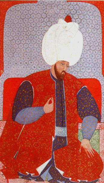 A sultan with a very ornate red vest over a long kaftan; his very large hat is topped with a red jewel.