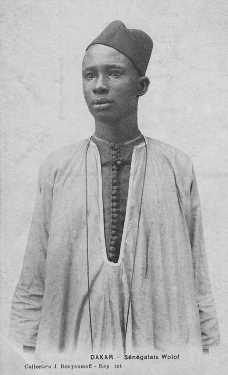 A young man in a fez from Dakar wearing a Senegalese Wolof, of kaftan. Image via Pinterest.