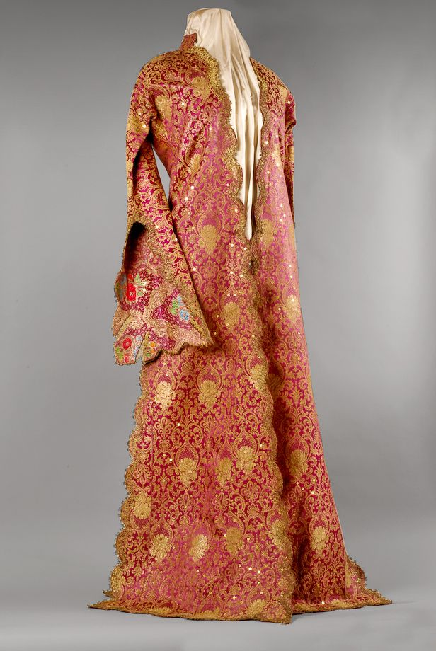 A gorgeously ornate robe/kaftan from Armenia, in gold and red brocade. The sleeves are gored, but also limned in embroidery. Gorgeously edge work all around, goes down to the floor.