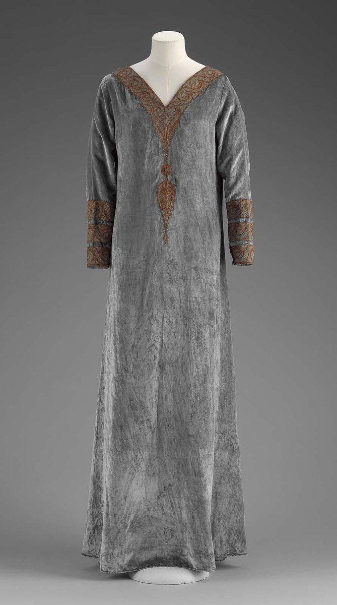 """Blue-green silk velvet gown, embroidered at cuffs and neckline in imitation of North African or Middle Eastern caftans, chain-stitched areas in gold metal-wrapped thread, outlined in couched cord of twisted orange silk and gold metallic thread, with trompe-l'oeil pendant effect at center front. Tan silk plain weave lining. Printed silk label at back of neck: """"Babani / 98 Bd Haussman / Paris"""" - Boston MFA"""