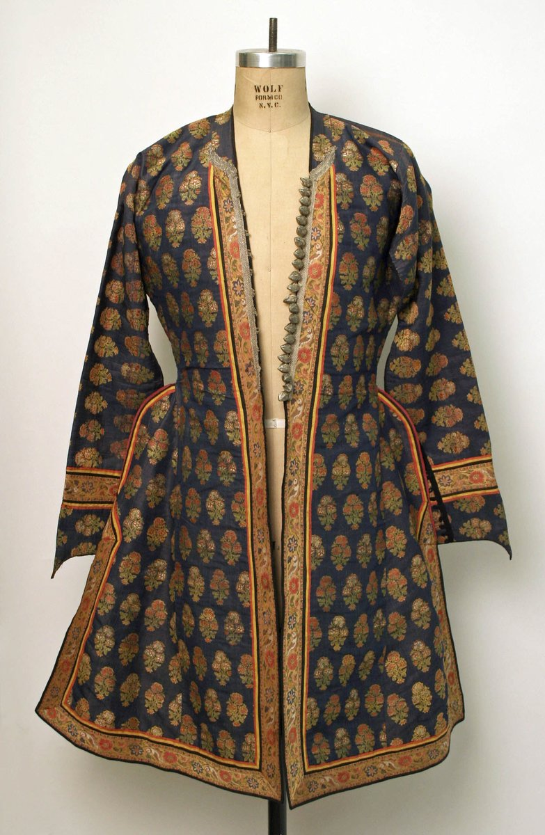 A shorter kaftan with embroidery all around it. The brocaded material features flowers, and it looks cut on the sides to allow for freer movement. The sleeves are long and bordered with additional flower motifs. Met Museum, public domain.