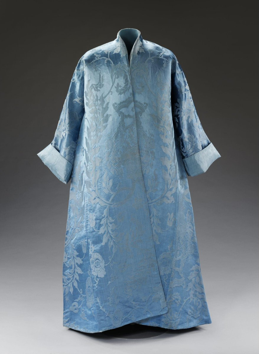 ©Victoria and Albert Museum, London - The night gown is made up using a blue silk damask with a large repeating design of a Chinese incense burner among acanthus-like foliage. It is lined with blue silk taffeta. It is of simple T-shape construction with no fastenings. There are no shoulder seams, so the design of the silk is in the correct orientation at the back, but appears upside down as it comes over the shoulders and down the front.  The loom width of the damask is 71 cm (28 inches). This width is consistent with it having been woven on a Chinese rather than European loom, as the design suggests.