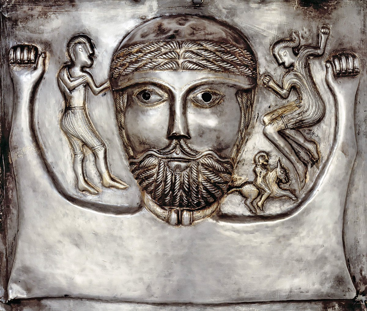 A Celtic relief with a woman, a man, and a large man in the middle with two fists up, rocking and rolling. Silver, with a torque around his neck. Also there is a guy on a horse/dog on his shoulder. Public domain.