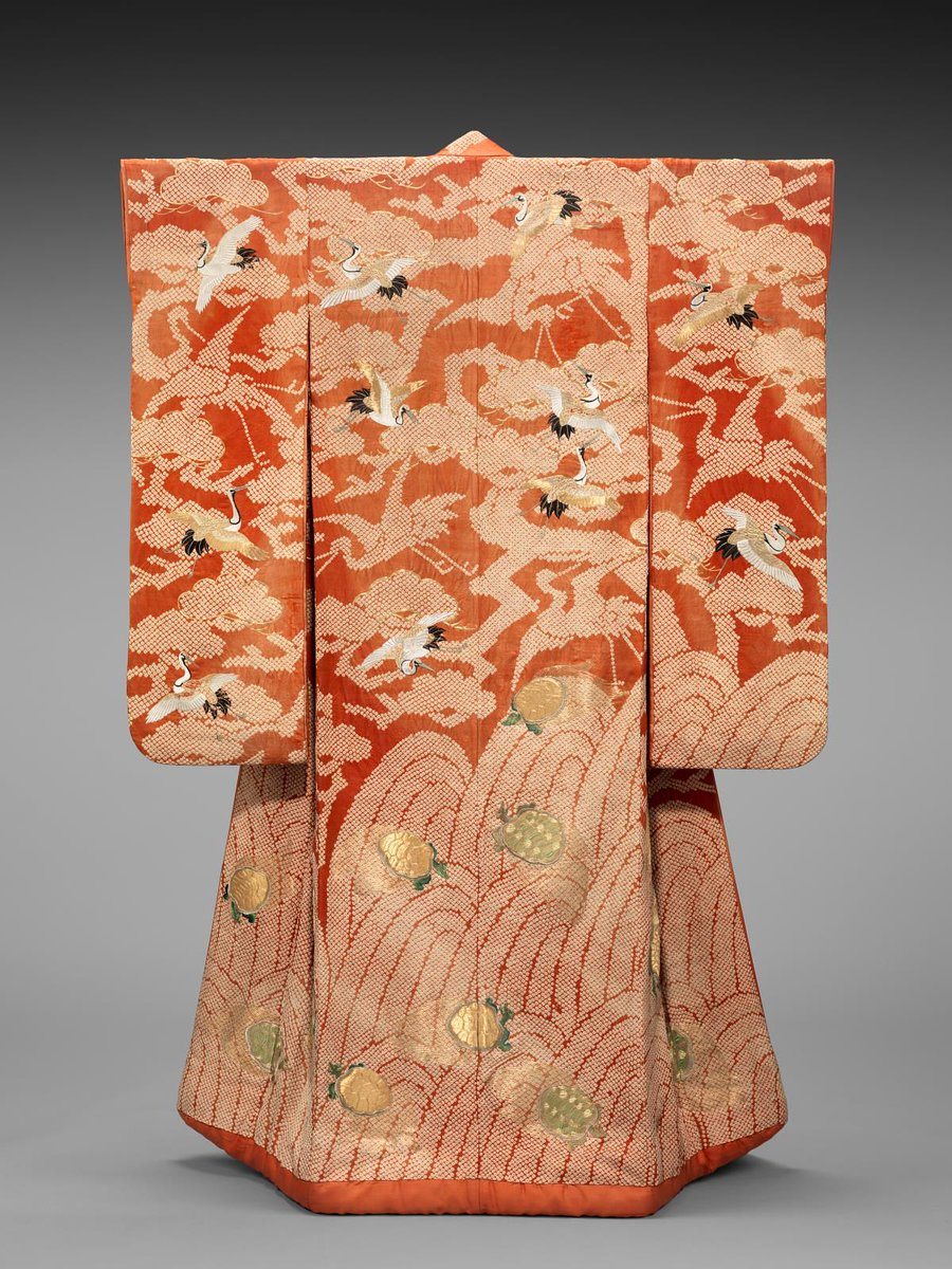 Long-sleeved outer robe (uchikake), probably for a wedding, of reddish-orange silk damask with design of tie-dyed waves at bottom embroidered with tortoises (minogame) and tie-dyed pine trees above embroidered with flying cranes (tsuru); lined with reddish-orange silk and padded at the hem. BMFA, public domain.