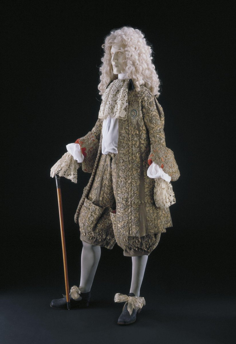 ©Victoria and Albert Museum, London - Coat and breeches of brown (originally a dark purple-brown) woollen broadcloth, interlined with linen and embroidered with silver and silver-gilt filé, and parchment wrapped in silver and silver-gilt strip in a pattern lilies and honeysuckle. The coat is lined with crimson silk taffeta. It has a round neckline bound with a narrow strip of the broadcloth, straight front edges, curving 2-piece sleeves ending between elbow and wrist, and narrow skirts below the waist. Each sleeve turns back to form a long narrow cuff with curved ends, revealing the crimson lining which is embroidered with silver purl, silver and silver-gilt filé in a pattern of large scrolls and leaves. There is an opening in each side seam at hip level and a horizontal pocket low on each front, fastening with 10 worked buttonholes and 10 buttons with a wooden core covered with silver and silver-gilt filé.