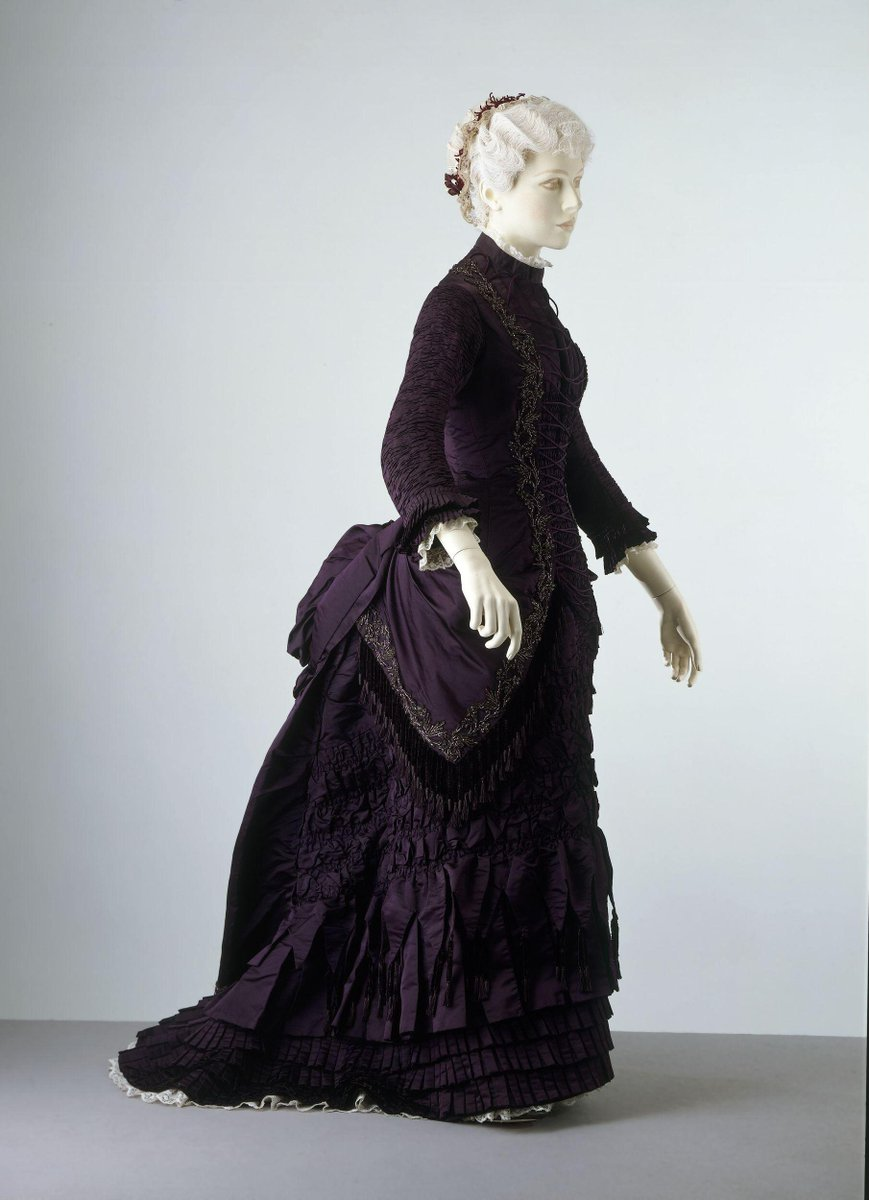 ©Victoria and Albert Museum, London - Satin dress trimmed with applied beading. High round neck. The dress fastens at the back from the narrow band collar to the hips with silver-plated buttons in a Florentine design. The tight, three-quarter sleeves are entirely gauged, trimmed at the cuffs with two rows of pleated bands. The front is fitted to the figure as far as the hips, and is designed to suggest a jacket. It is trimmed round the edges with motifs in iridescent beads and worn over a pleated and ruched stomacher front with a mock lacing. At the hips, it is draped back into paniers which knot over the train. The skirt is ruched as far as the knees where it is arranged in pleated tabs with pendant chenille tassels mounted over crenelated tabs and bands of pleats. The sleeves and the bodice, which is boned, are lined with white glazed cotton, and the skirt with mauve polished cotton. The back breadth is lined with stiffened cotton and held in place with tapes. Machine and hand sewn.